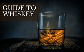 Glass of liquor on table (caption: Guide to Whiskey)