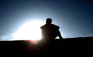 Man sitting on hill alone