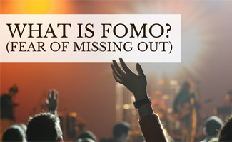 Person waving hand in crowd: What is FOMO (Fear of Missing Out)?